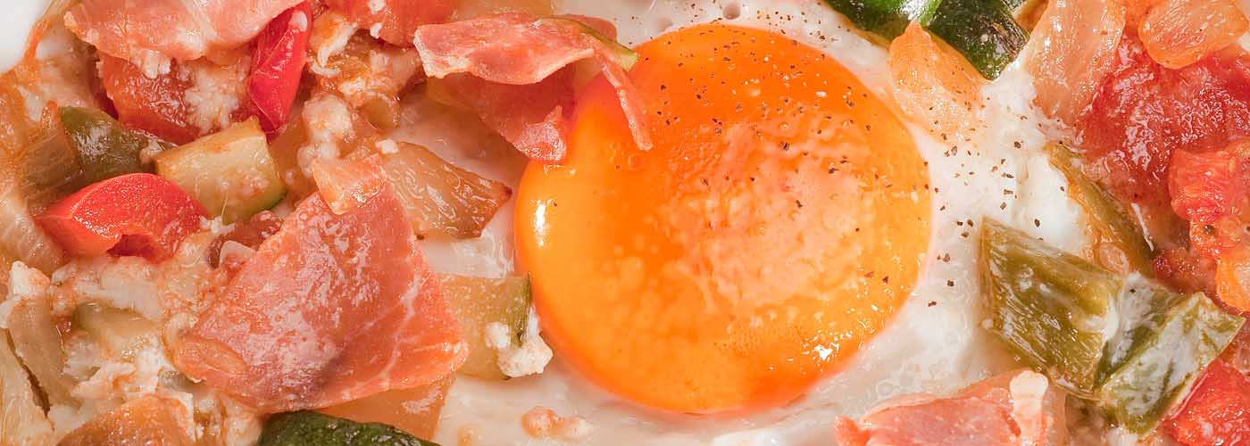 Spanish recipe: Baked eggs with Spanish vegetables and Serrano ham. Photo by: Toya Legido/©ICEX.